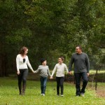 Family of four holding hands and walking through the park