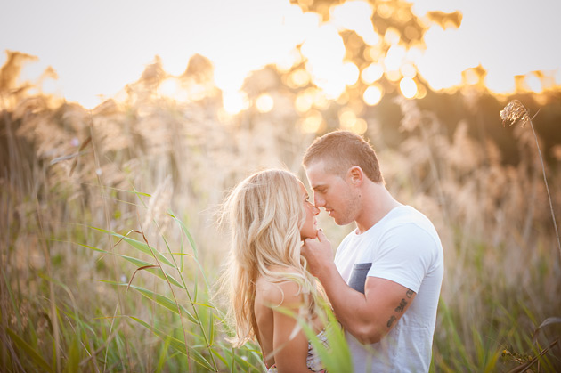 couple looking at each other surrounded by long grass with the sunlight filtering in behind them