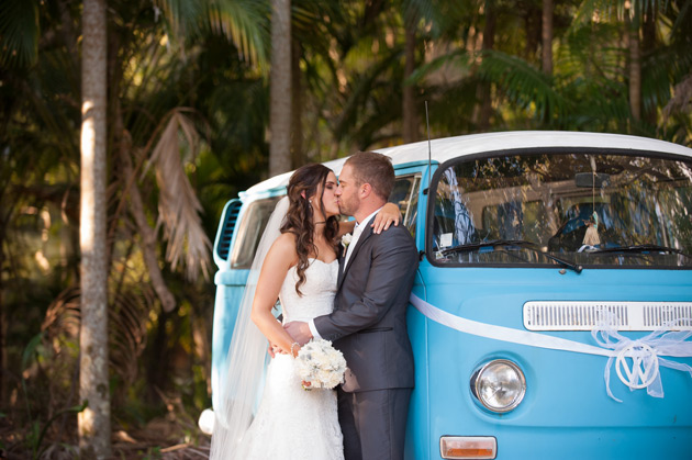 newlyweds kissing by car