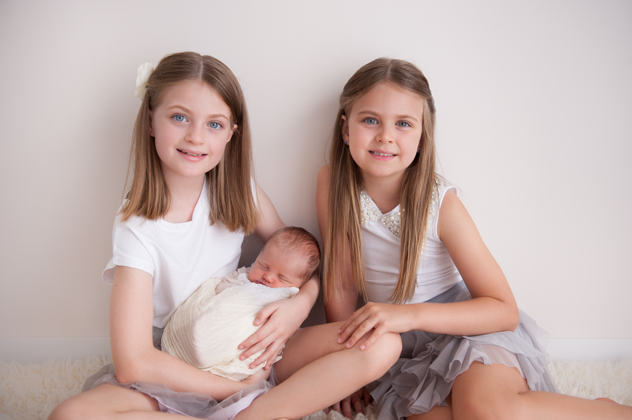 newborn baby girl with sisters
