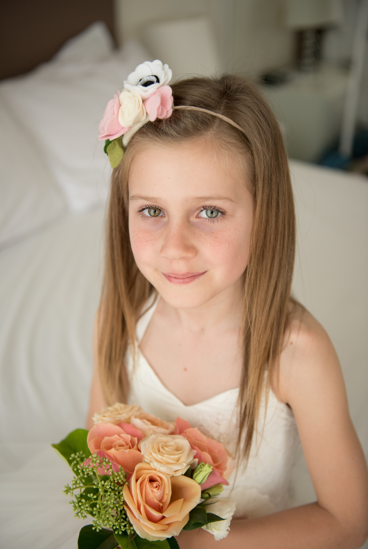 Flower girl_looking_at_camera_holding_her_flowers_smiling