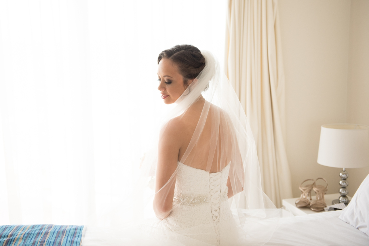 Stunning_bride_sitting_on_the_bed_with_veil_over_her_shoulder_looking_back