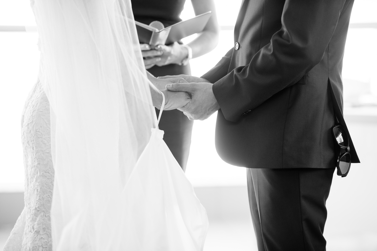 Bride_and_groom_holding_hands_during_the_ceremony