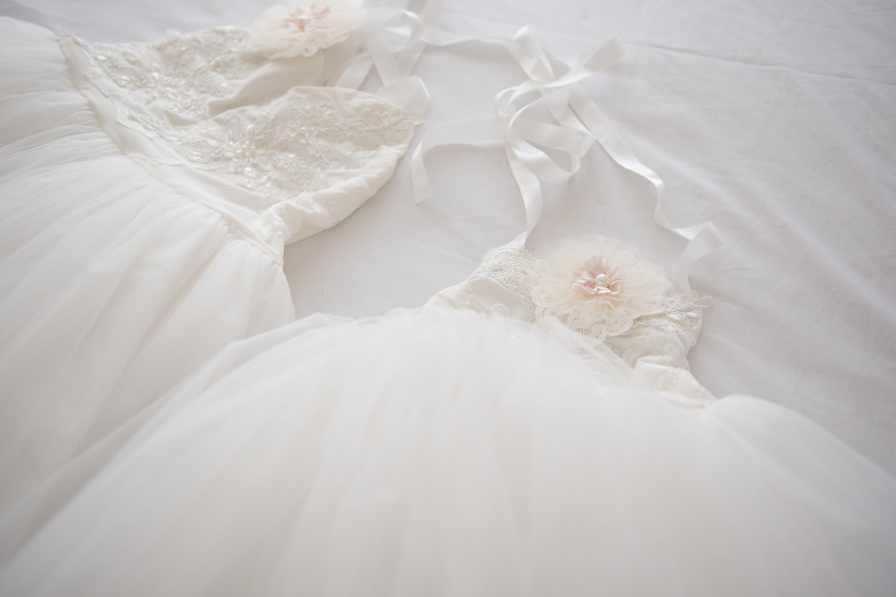 flower girl dresses lying on a bed