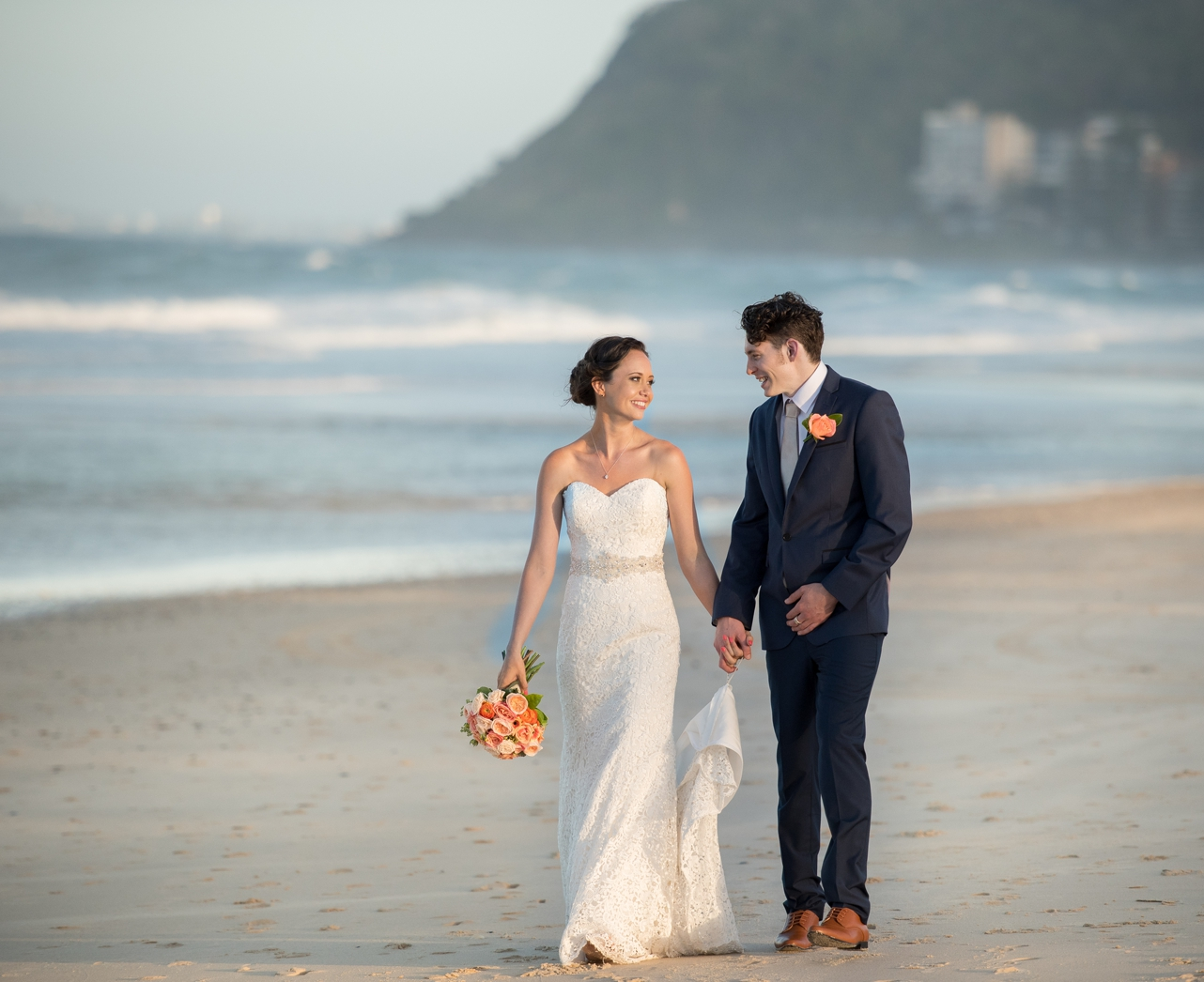 Bride_and_groom_walking_along_the_beach_groom_holing_his_brides_dress