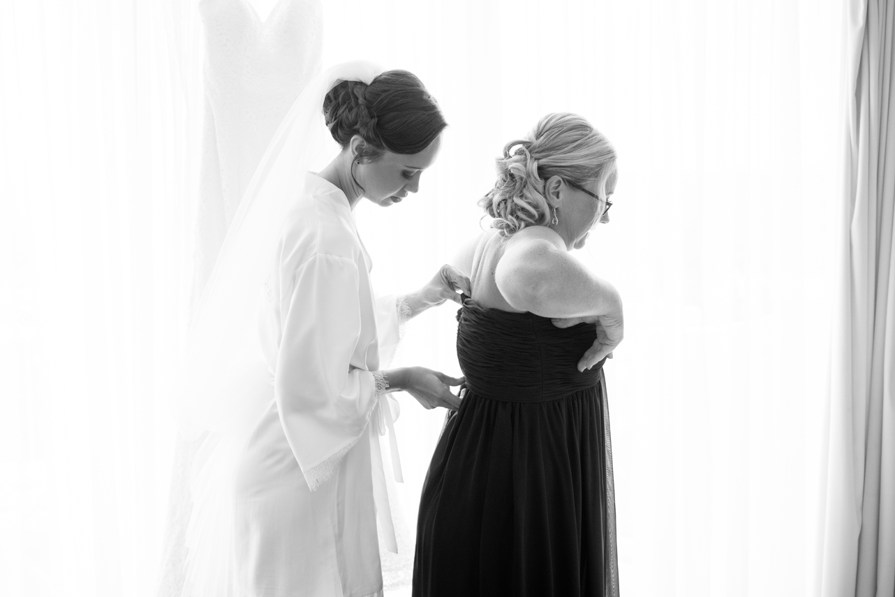 Bride_helping_her_bridesmaid_get_into_her_dress