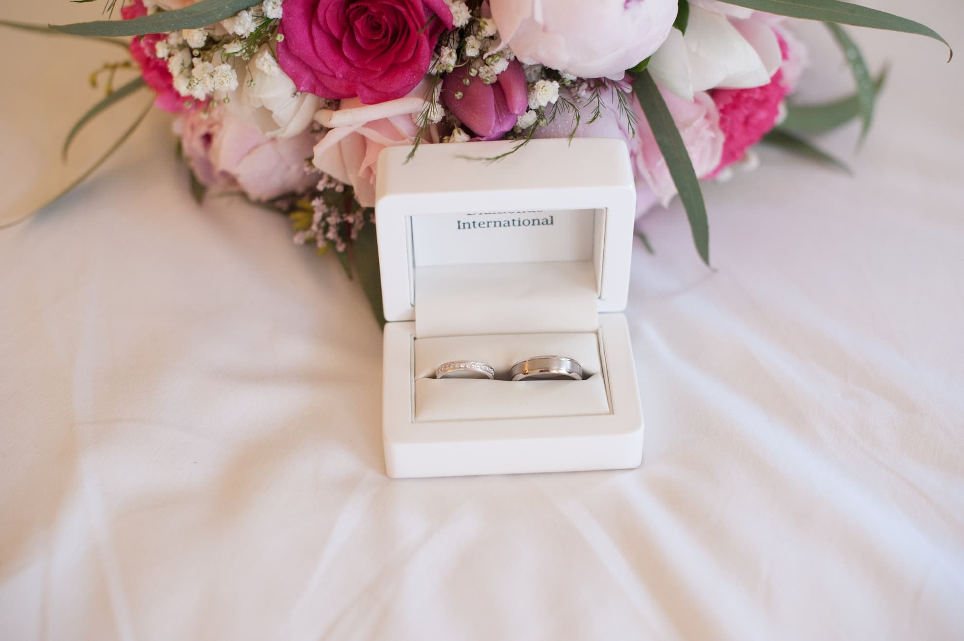 wedding-rings-sitting-on-the-bed-next-to-flowers