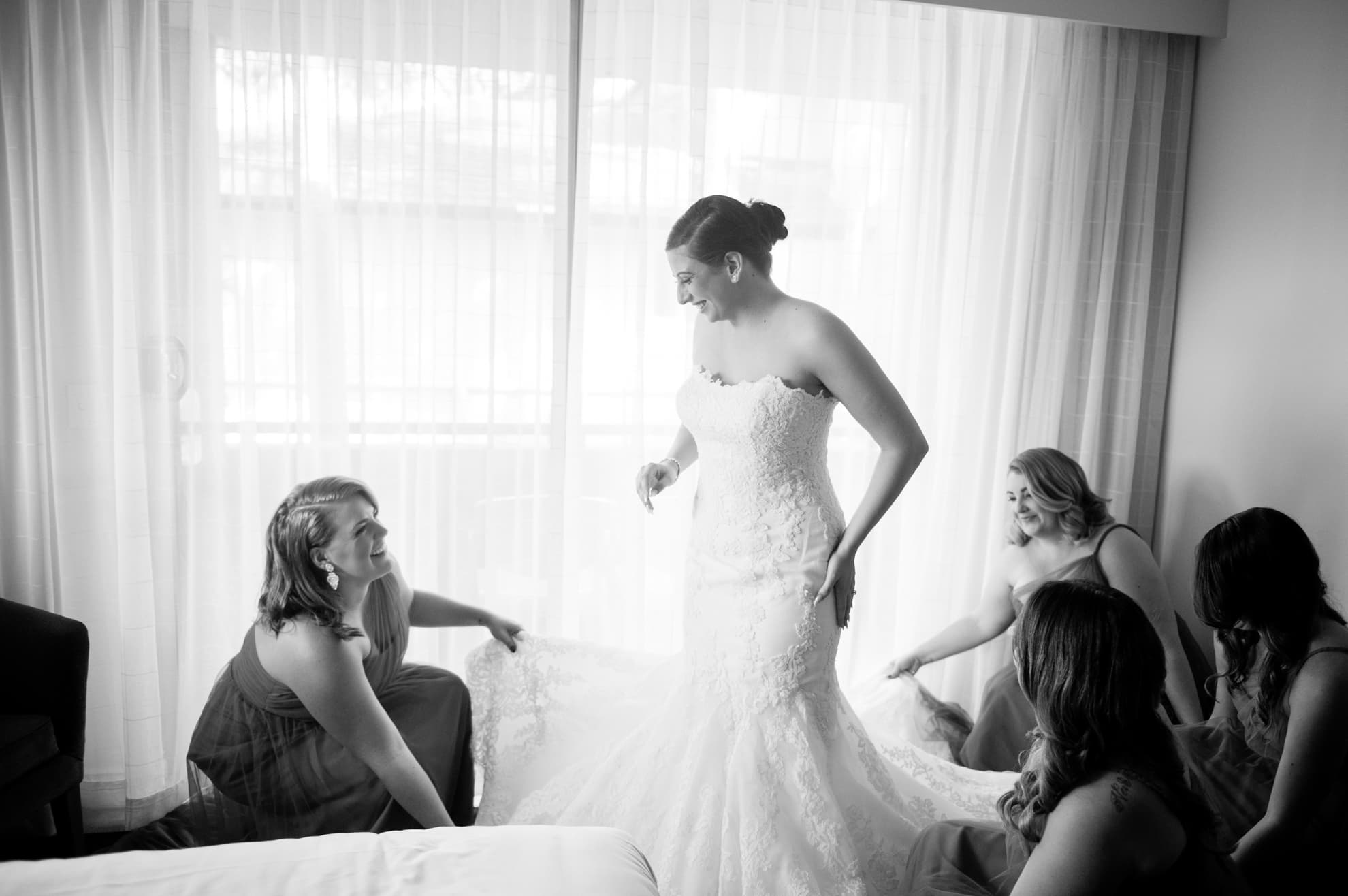 bridesmaids-help-the-bride-into-her-dress-bride-looks-at-them-smiling