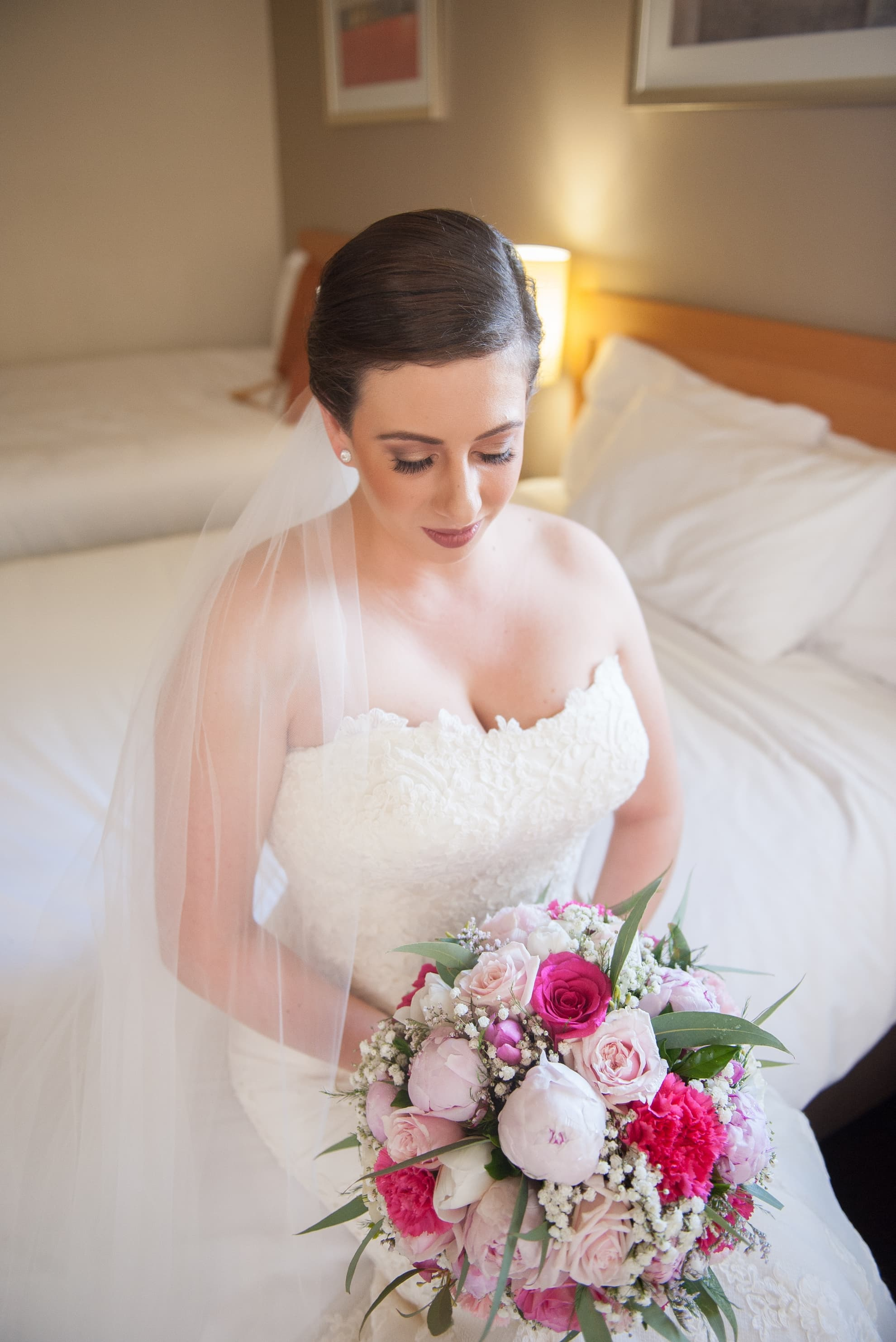 bride-sitting-on-the-bed-looking-down-at-her-flowers