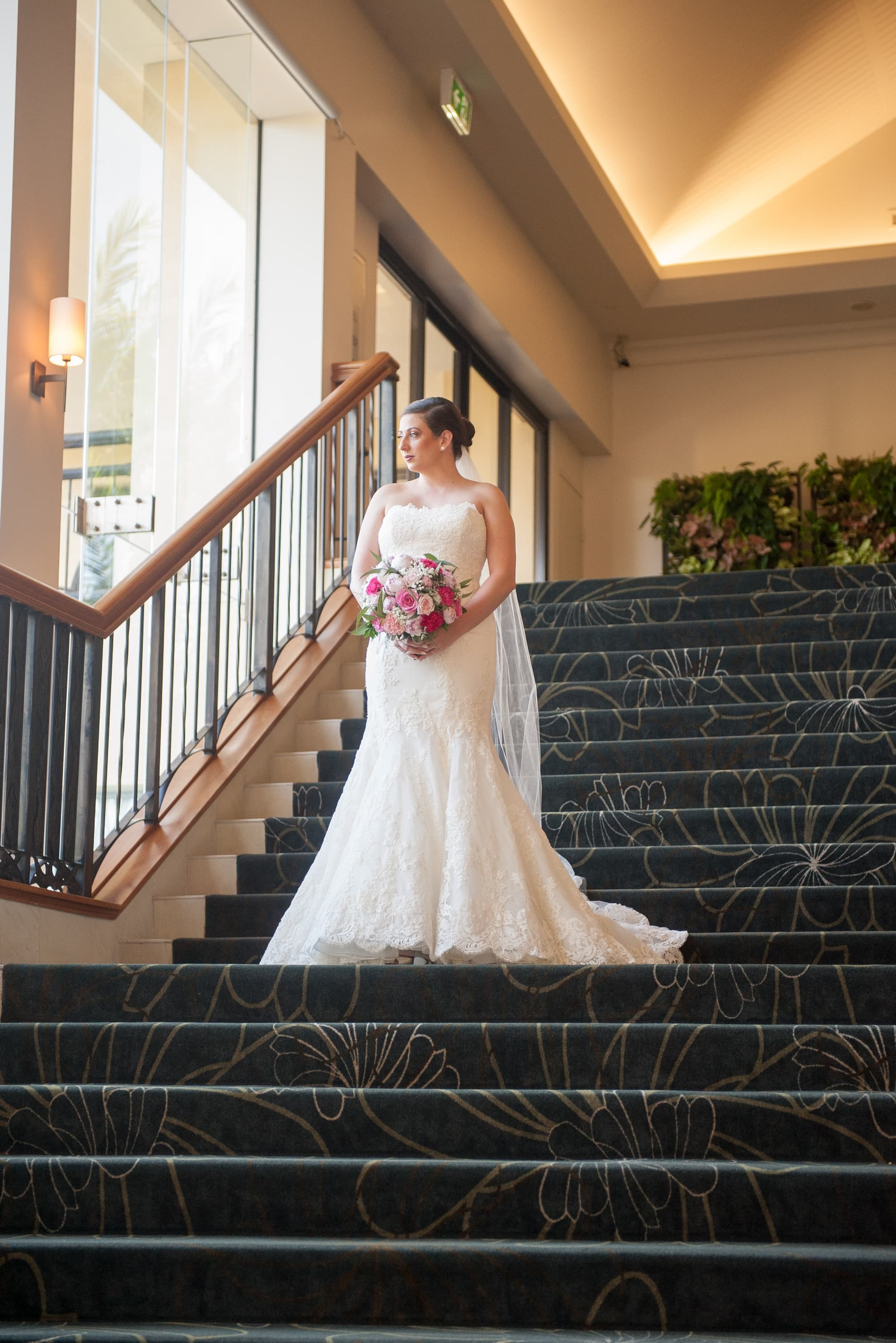 bride-standing-in-the-middle-of-staircase-looking-out-the-window