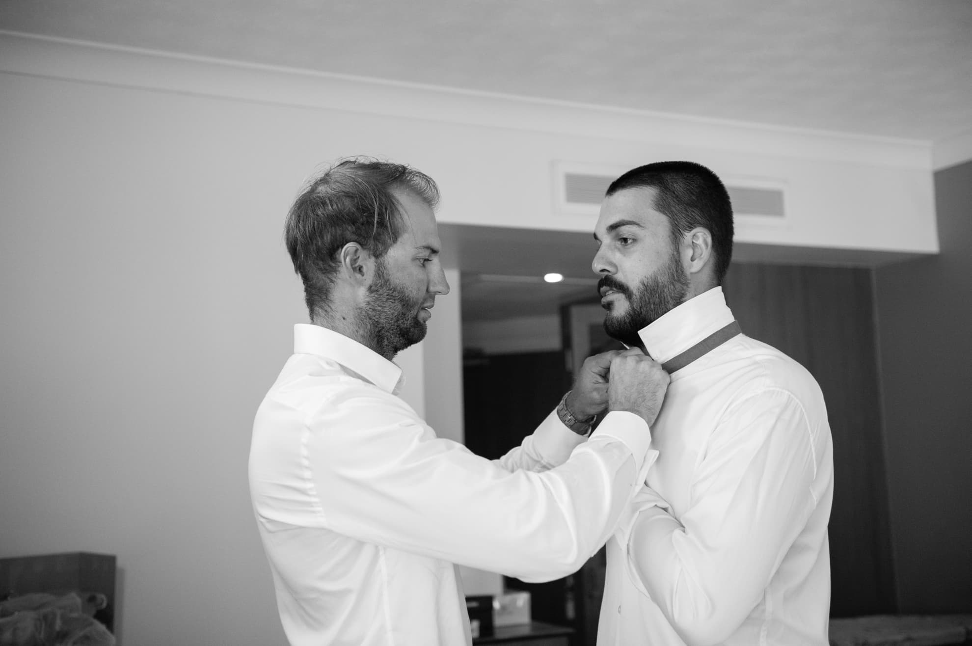 Groom-helping-dress-the-groomsmen-with-his-bowtie