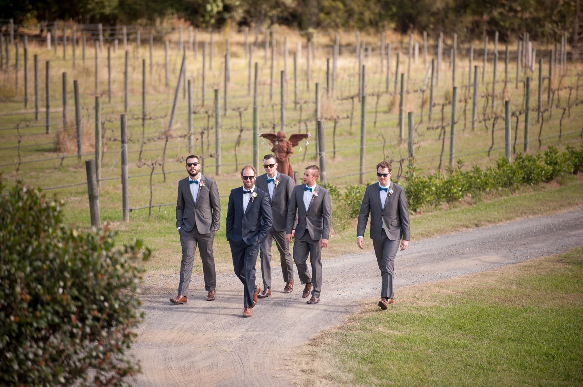 groomsmen-all-walking-in-a-line-to-the-ceremony-on-a-dirt-path