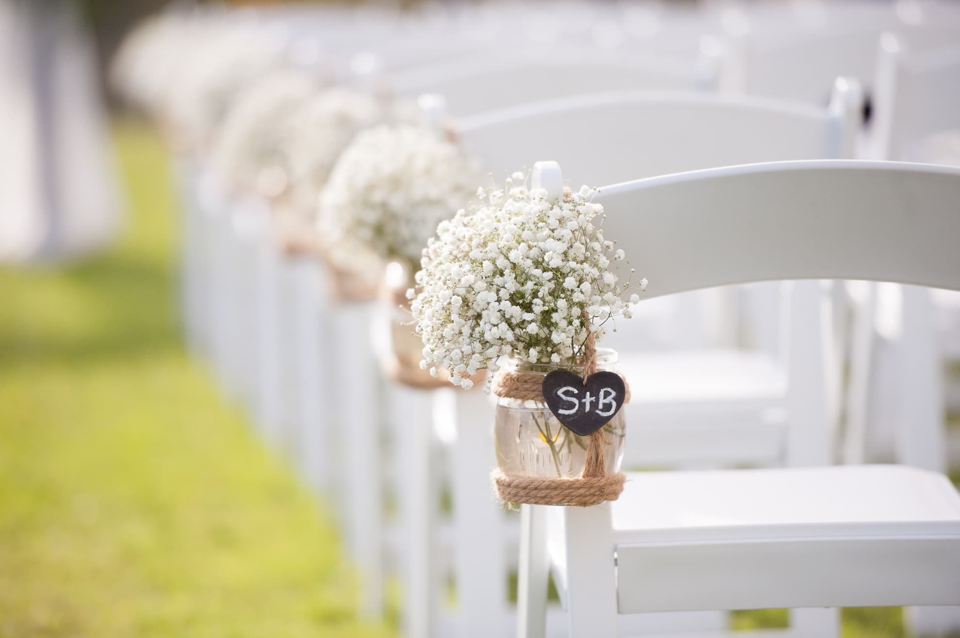 baby-breath-in-jars-attached-to-the-chairs-at-wedding-ceremony