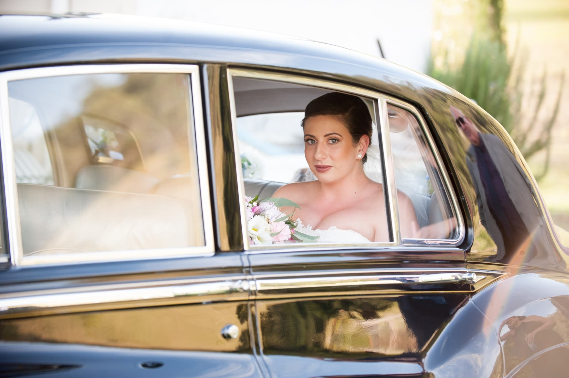 bride-smiling-looking-at-the-camera-out-of-the-car