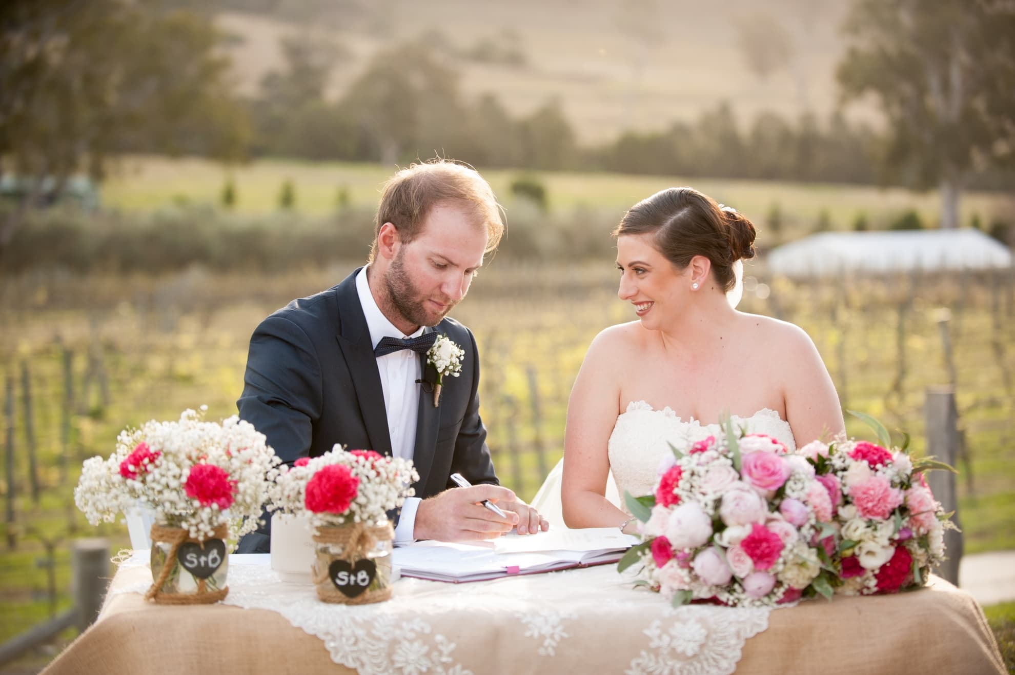 bride-and-groom-looking-at-each-other-smiling-signing-the-marriage-certificate