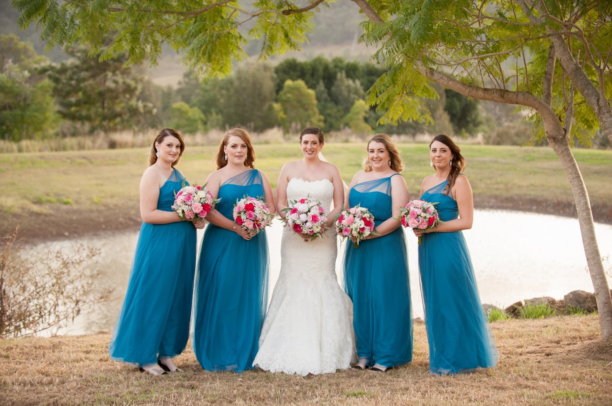 bridesmaids-and-bride-miling-looking-at-the-camera-with-the-mountains-and-dam-behind-them