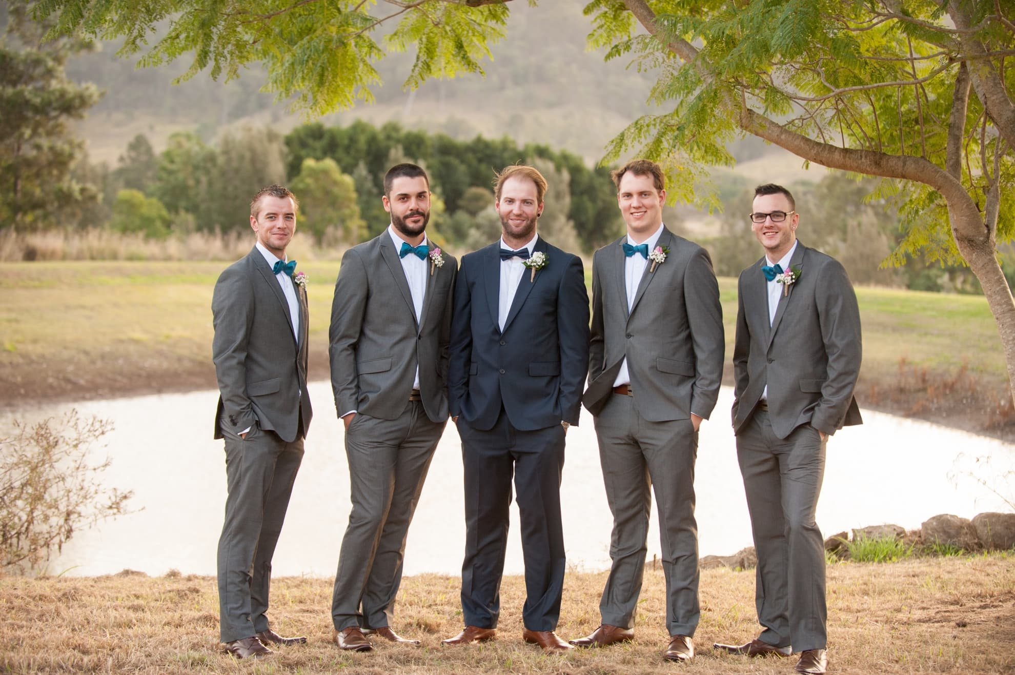 groomsmen-and-groom-with-hands-in-pockets-looking-at-the-camera