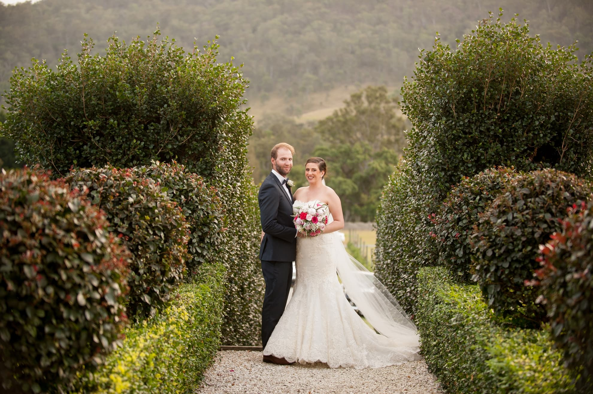 bride-and-groom-looking-at-the-camera-holding-each-other-standing-on-stone-path-with-trees-surrounding-them