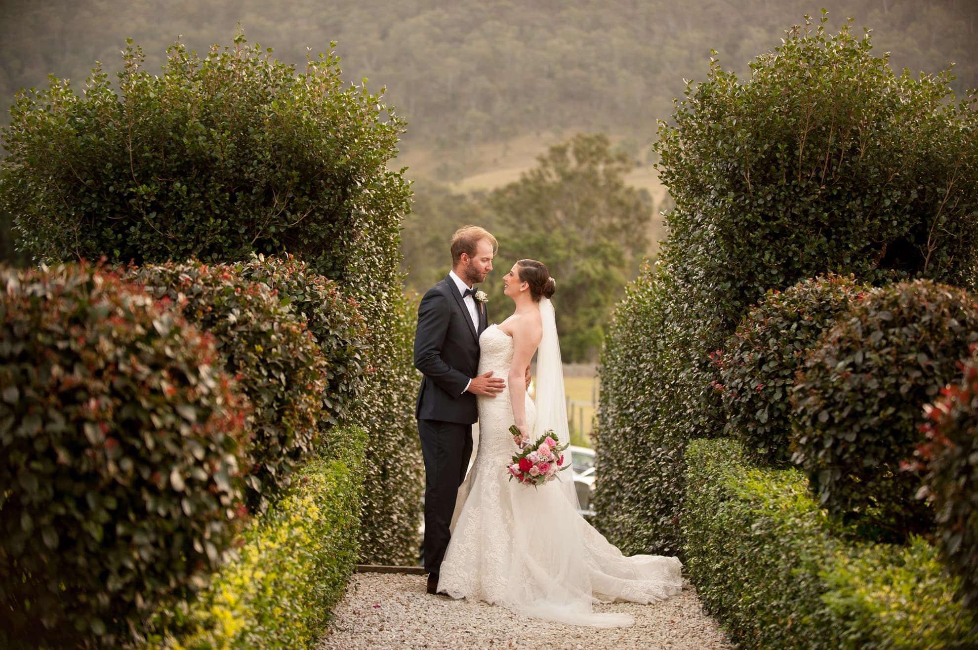 bride-and-groom-looking-at-each-other-and-holding-each-other-standing-on-stone-path-with-trees-surrounding-them