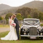 bride-and-groom-having-a-kiss-next-to-the-bridal-car-at-the-vineyard