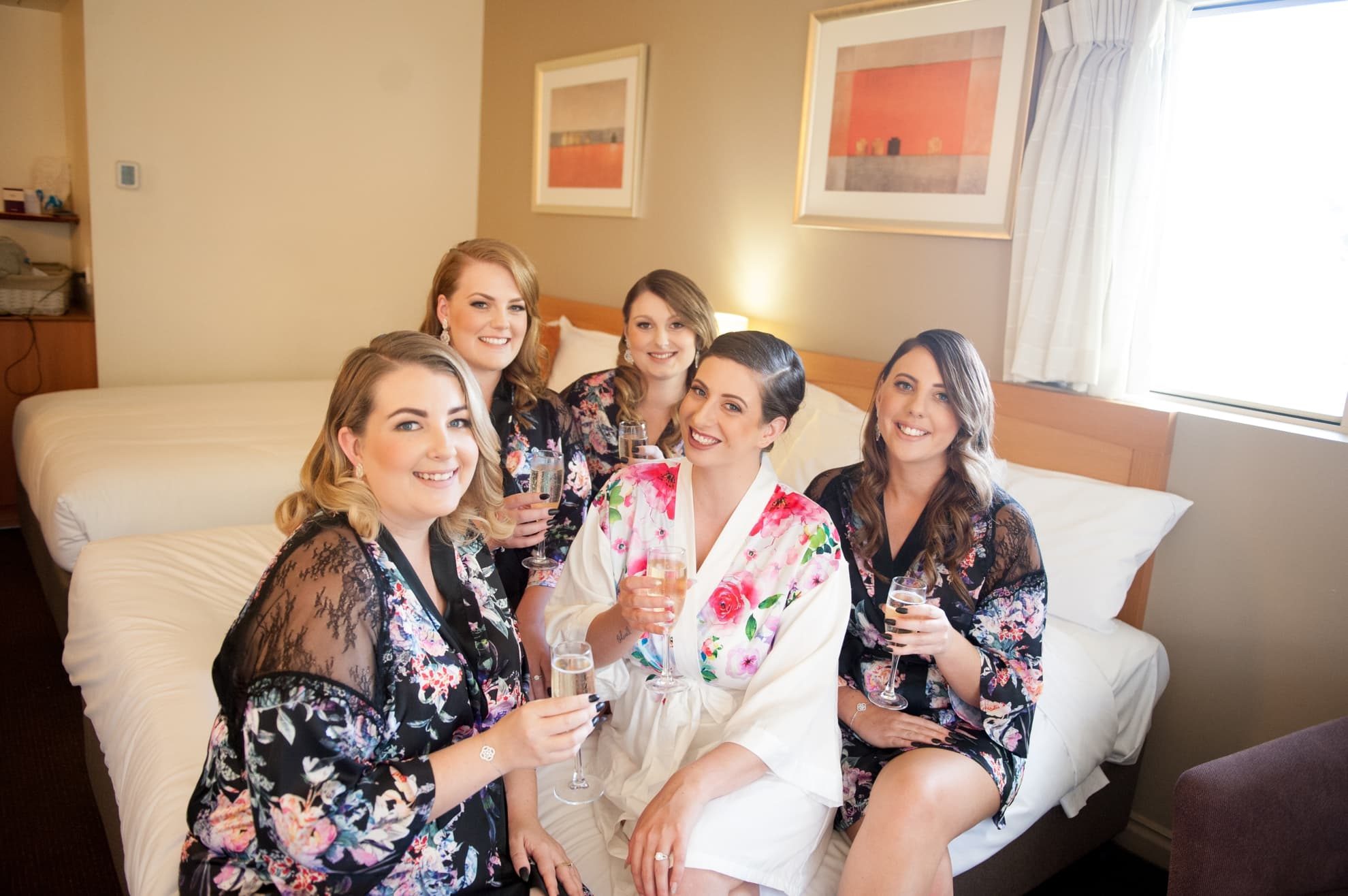 bride-to-be-with-her-bridesmaids-in-their-robes-smiling-before-they-get-dressed