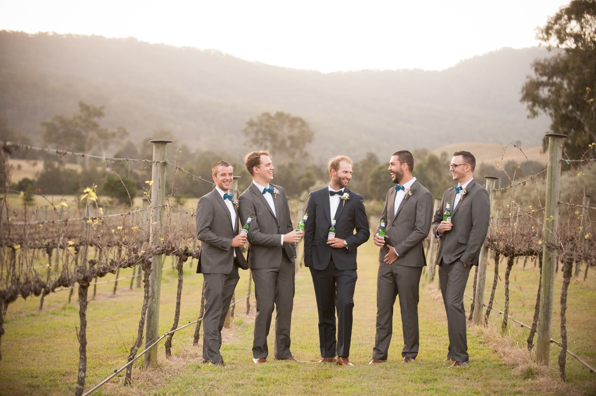groomsmen-and-groom-having-a-beer-together-in-the-vineyard
