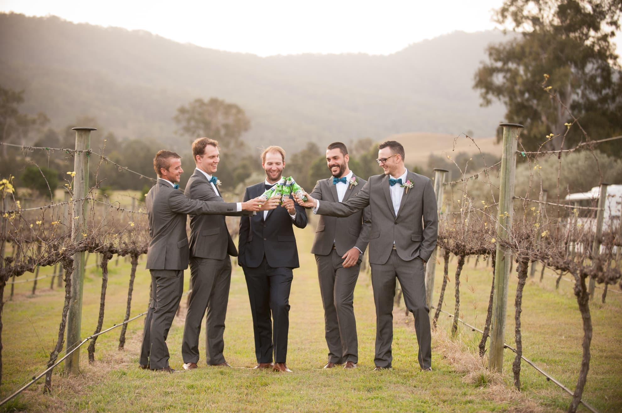 groom-and-his-groomsmen-having-a-cheers-with-the-beer-bottles-laughing