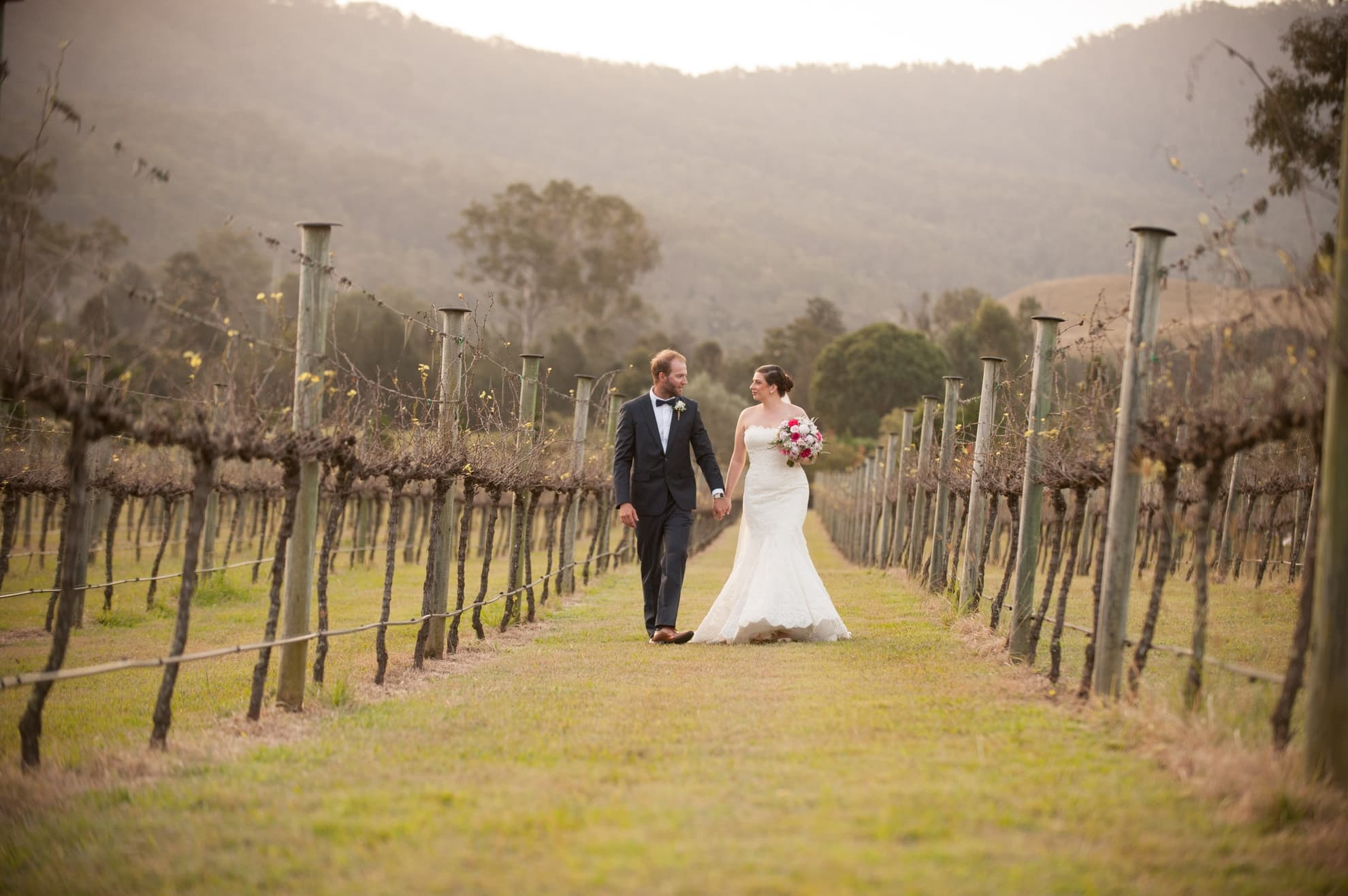 bride-and-groom-holding-hands-looking-at-each-other-in-the-vineyard