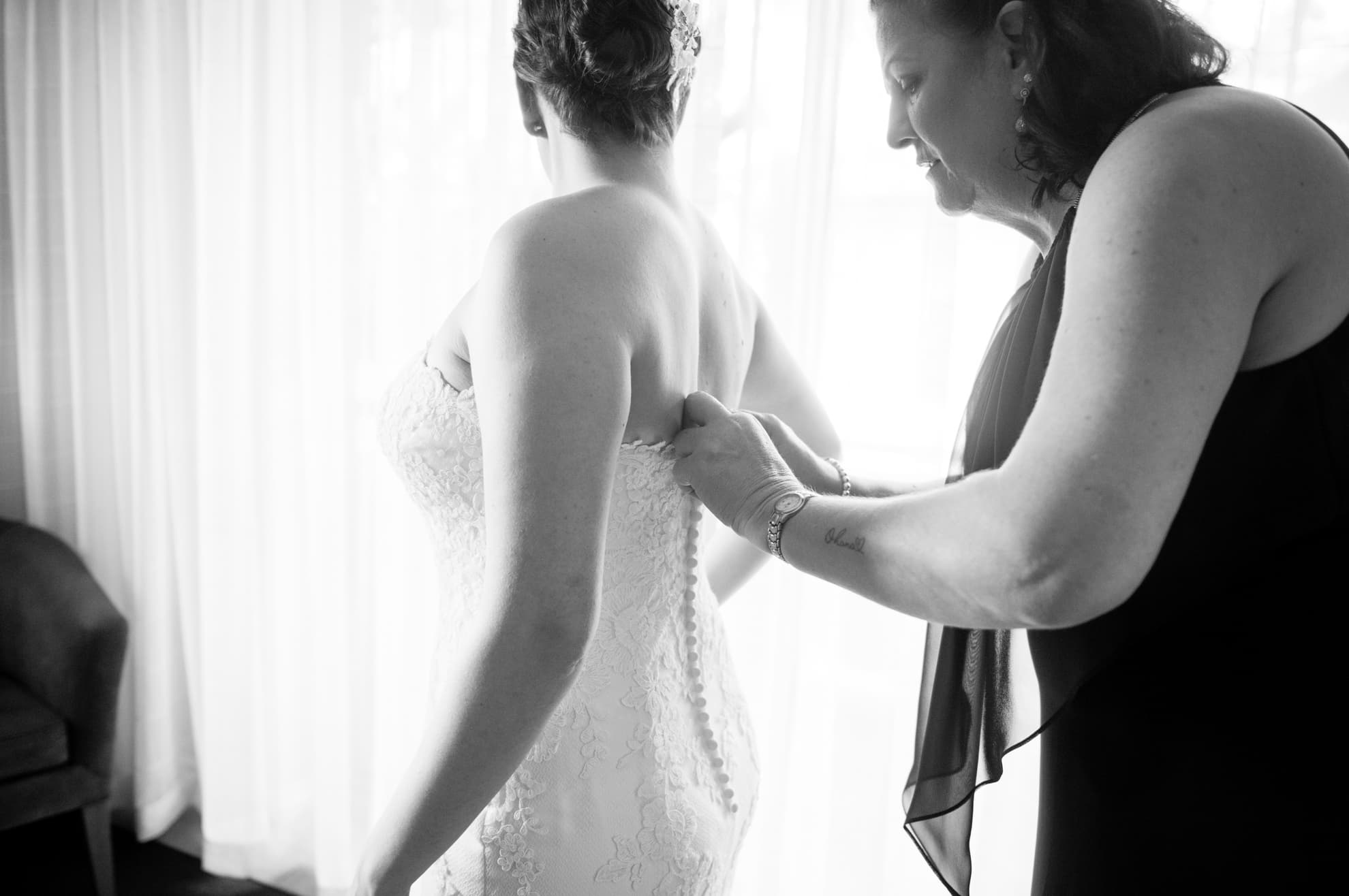 mum-helps-bride-into-her-wedding-dress